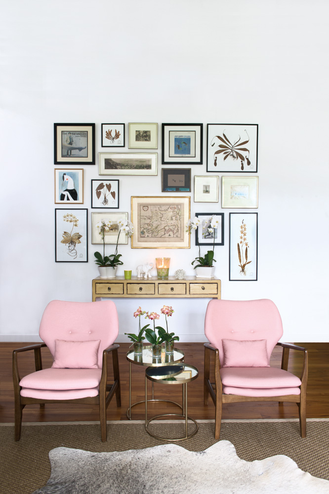 A pair of mid century-inspired chairs from Indigo Living upholstered by Albert Kwan from Wing Sun Upholstery frame the gallery wall perfectly.