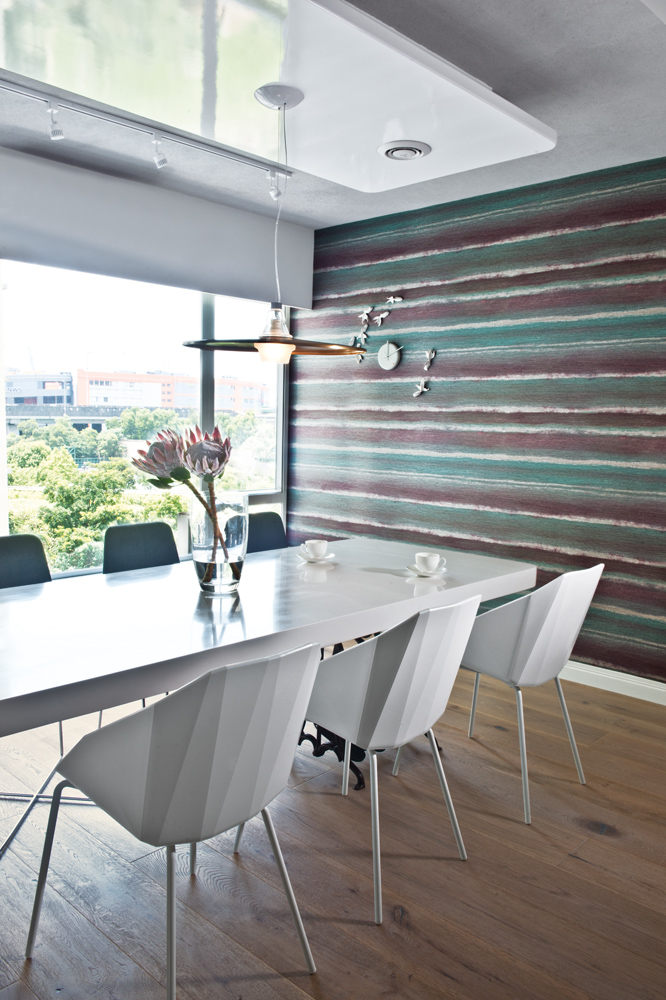 The green, teal and violet accent wall complements the verdant view from the picture window in the dining area.