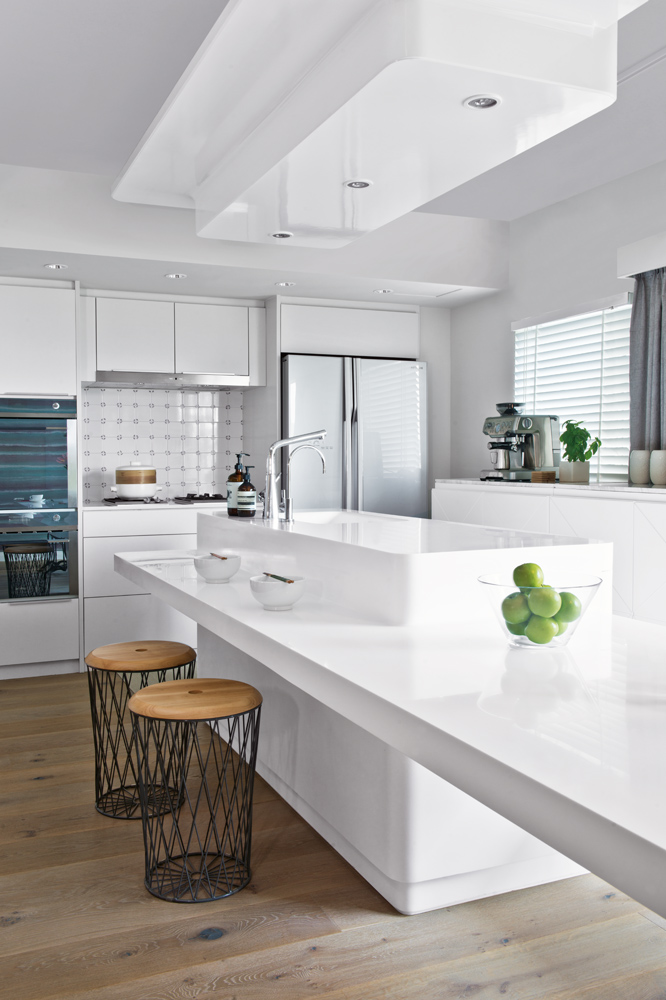 The colour white combines with clean, geometric lines in the multi-purpose kitchen, which is Wesley's favourite space in his apartment.