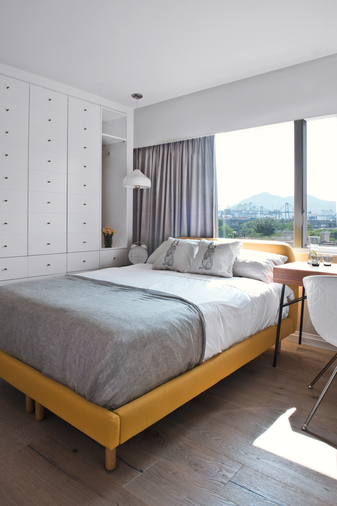 The mustard-yellow bed frame contrasts with the muted palette in the bedroom.