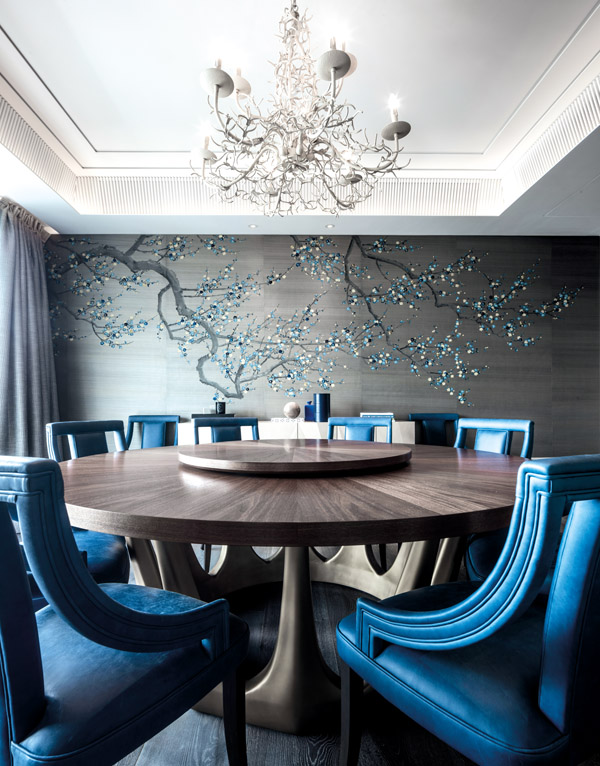 A hand-painted silk wallcovering with embroidered blossoms by Fromental sets the design direction for the dining room