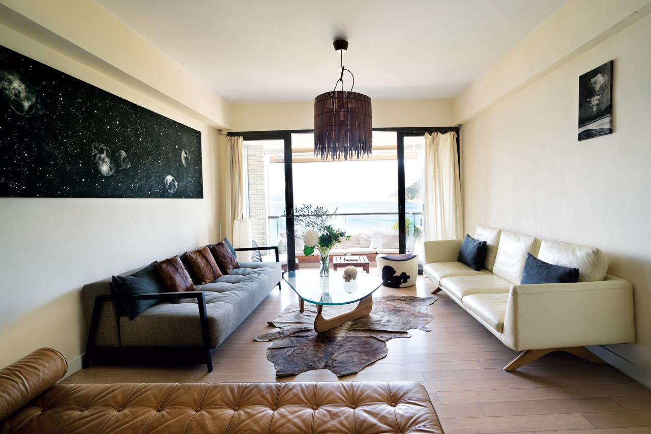 Lalie's penchant for neutrals, black and white, and materials such as leather shines in the living area; the white wall is sometimes used as a backdrop to project movies