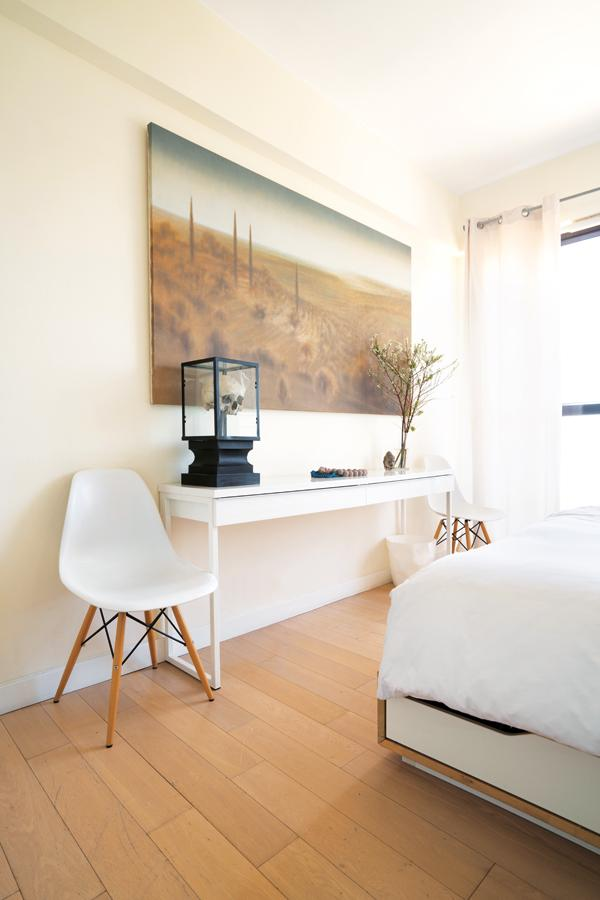 Two DSW dining chairs flank a sideboard in the master bedroom, where Toscani #1 by Didier Eberoni takes pride of place