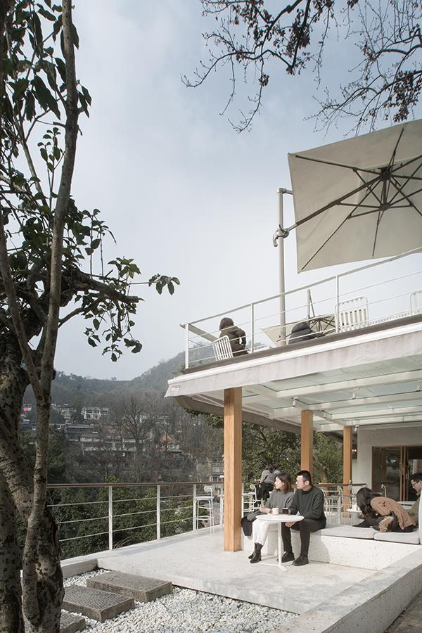 An open upper terrace with views of the surrounding nature further blur the cafe