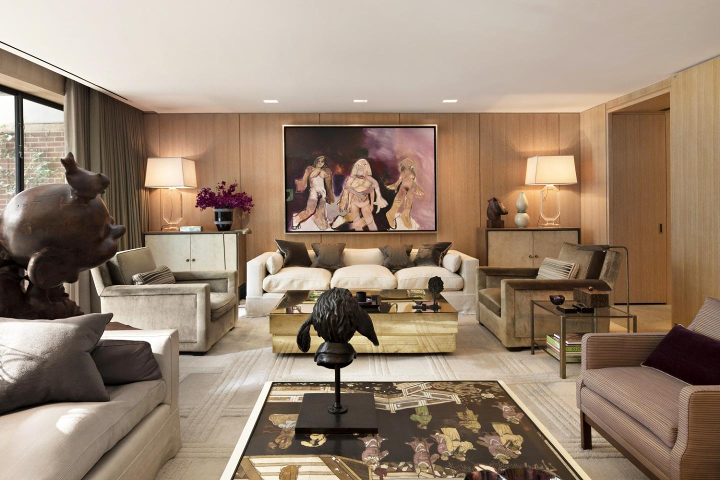 Oak wood wall panelling set the scene for the television room, where a painting by Richard Prince hangs above a custom-made sofa by Jonas and a brass Gabriella Crespi low table from Nilufar