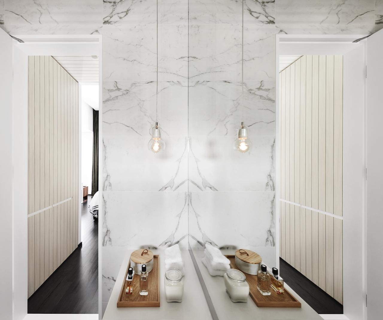 In the master bathroom, a pendant lamp from &Tradition complements white marble walls and floors