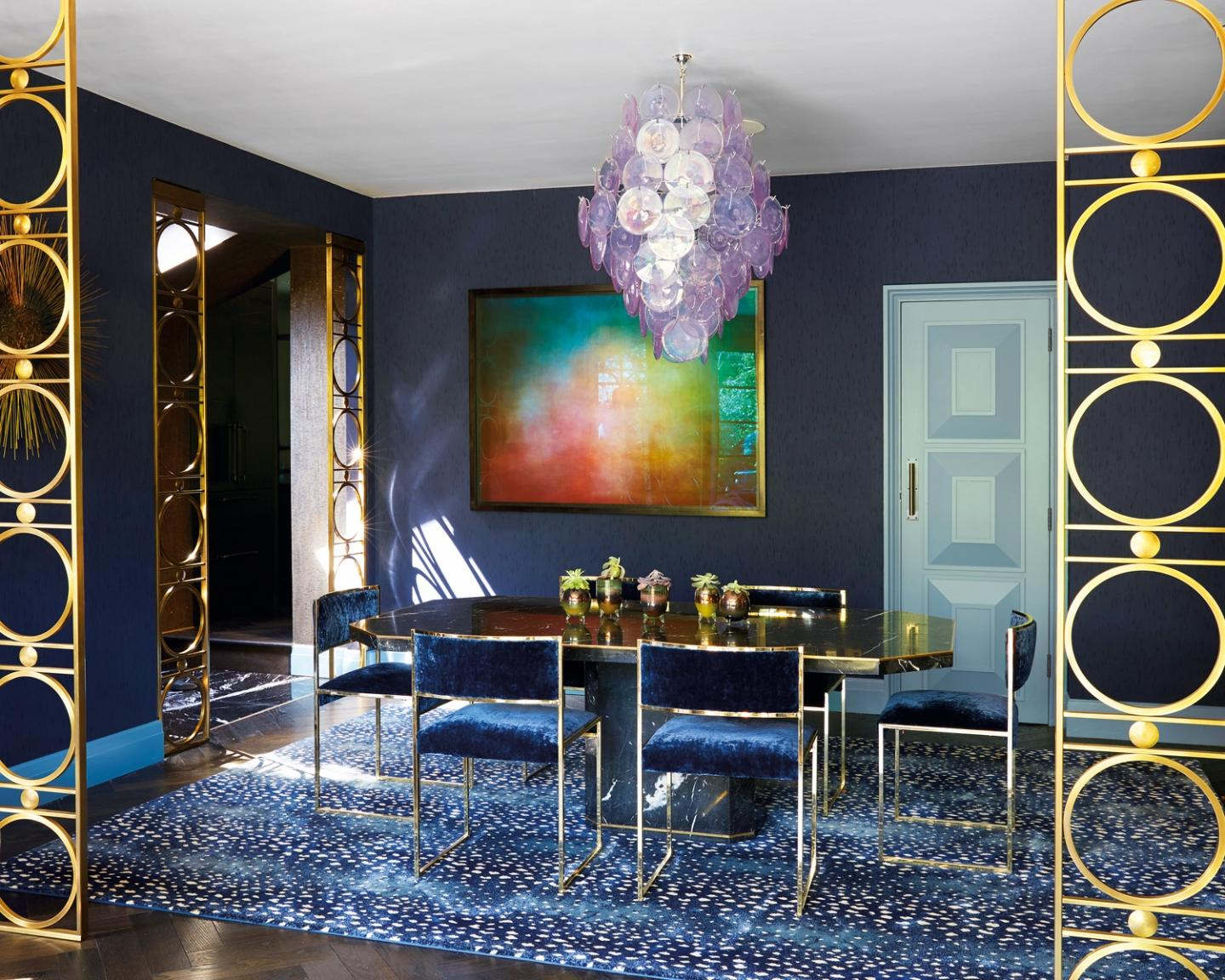 The dining room is an excercise in controlled contrasts, where a black marble table by Willy Rizzo intermingles with vintage chairs by Milo Baughman, a rug by Starck Carpets, a lilac disc chandelier by Vistosi and an artpiece by Jason Shulman