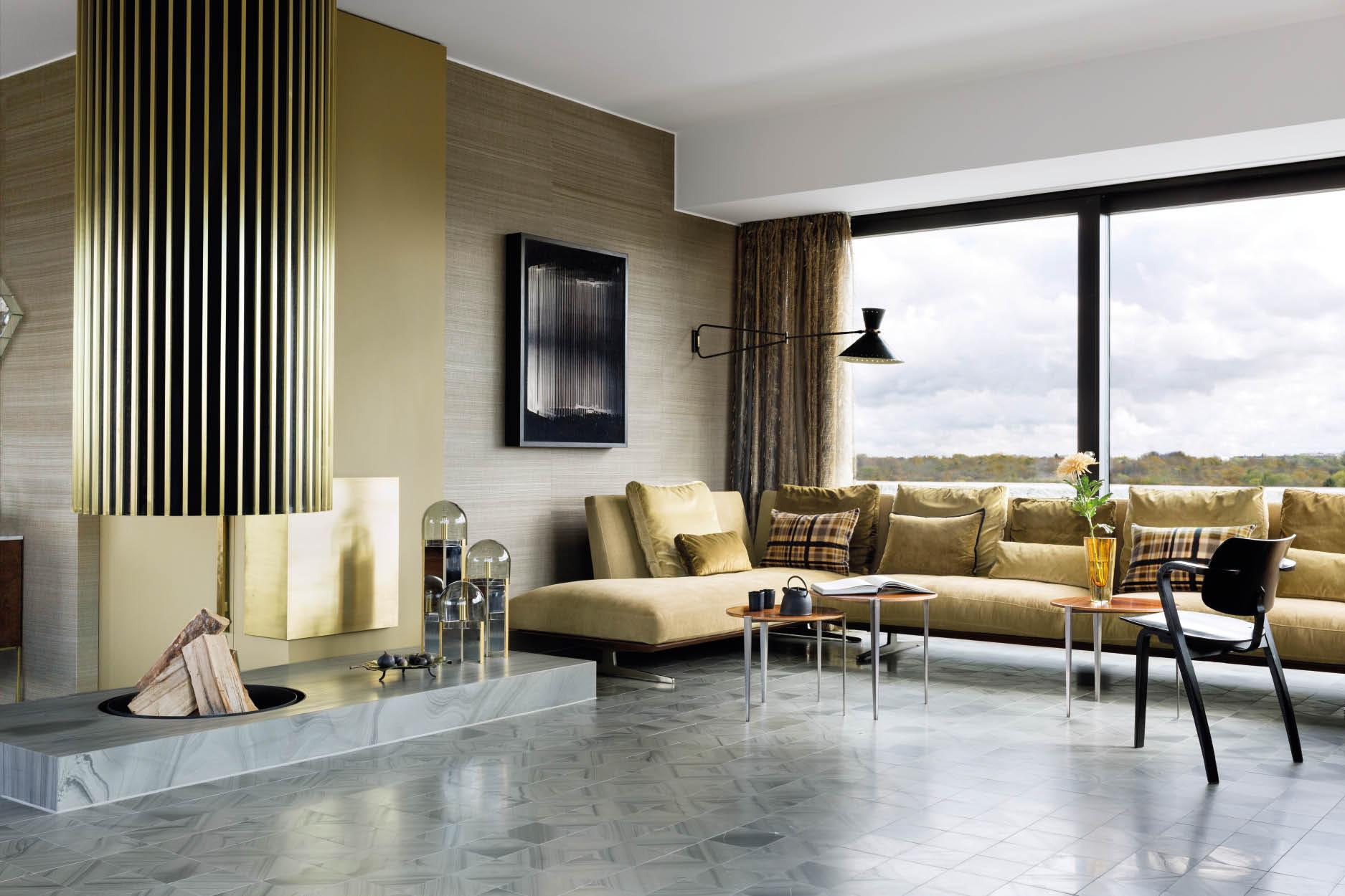 The living room features a grey natural stone floor, brass-coloured velvet fabrics and a gold floating fireplace