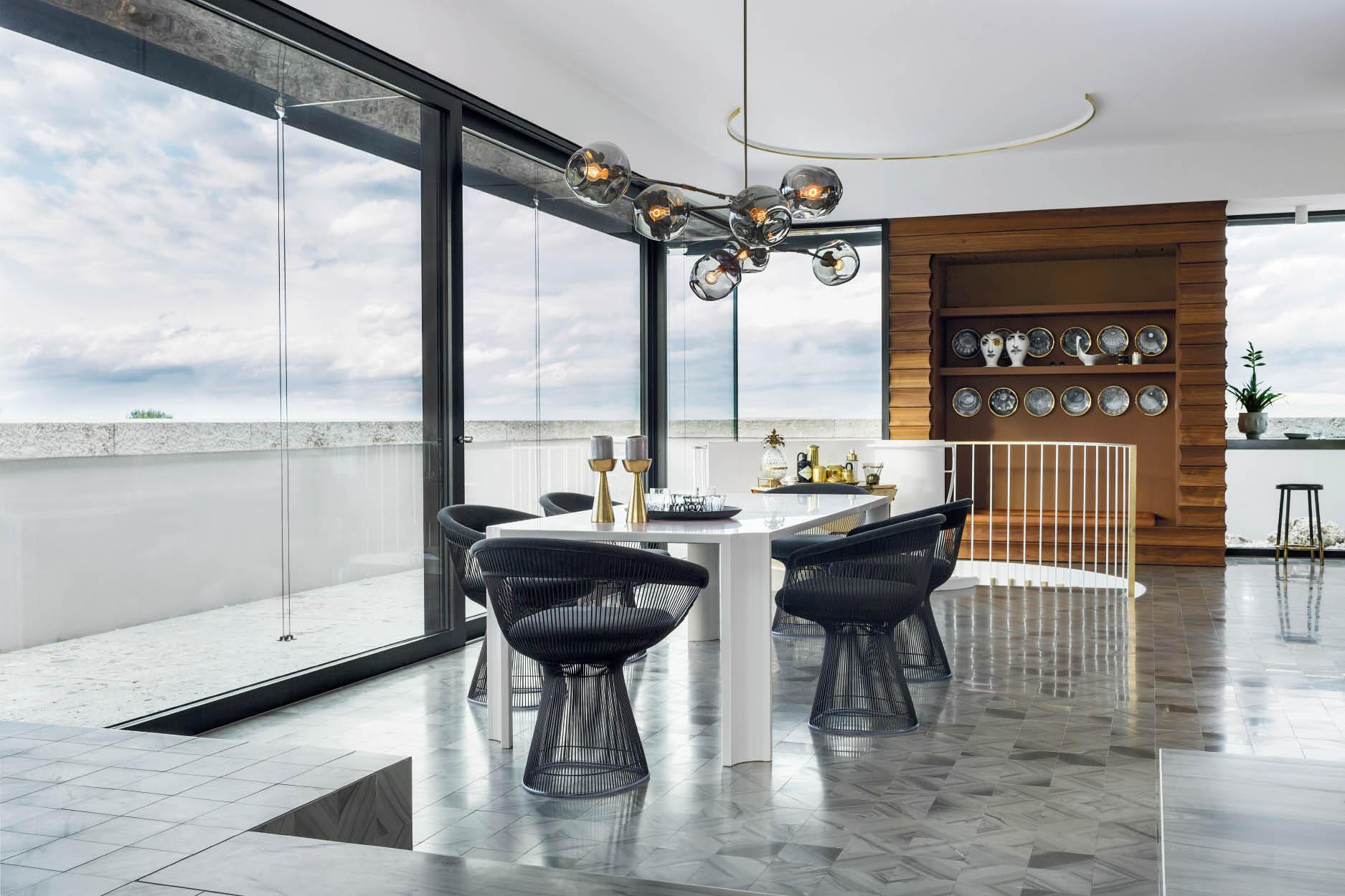A bespoke dining table is flanked by Warren Platner chairs