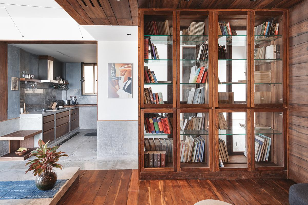 The entertainment den, elevated to delineate a completely separate space from the rest of the home, while housing storage underneath, also features a library. (Photo: The Fishy Project)
